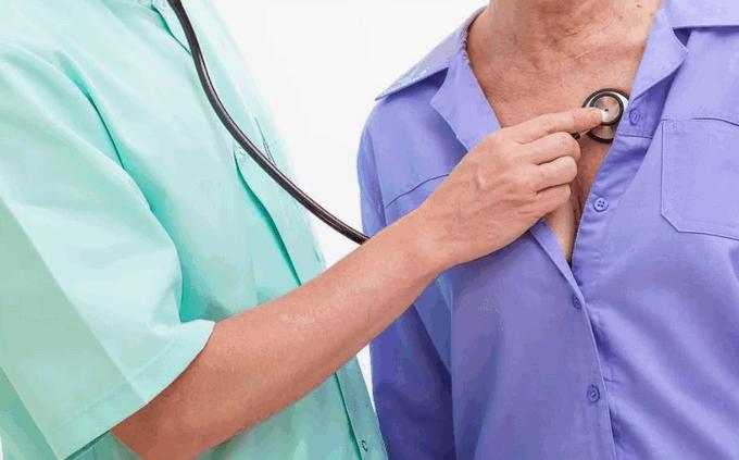 Врач прослушивает больного фонендоскопом